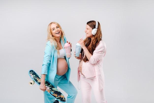 Zwei schwangere mädchen in türkisfarbenen und rosafarbenen anzügen mit saftgläsern, einem schlittschuh und kopfhörern stehen auf grauem hintergrund