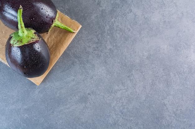 Zwei schwarze auberginen mit wassertropfen auf steinhintergrund.