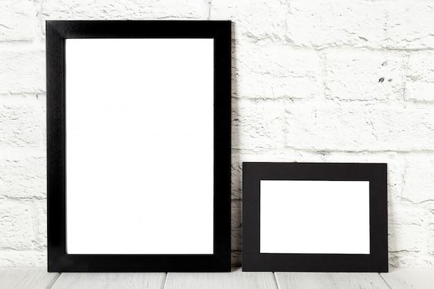 Zwei schwarze fotorahmen auf holztisch. modell mit textfreiraum