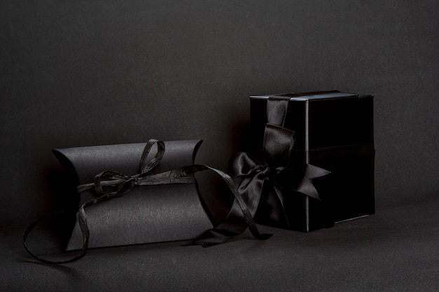 Zwei schwarze geschenkboxen mit bandschleife auf dunklem hintergrund