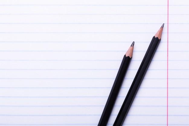 Zwei schwarze graphitstifte auf weißem blatt in der linie kopienraum zurück zu schule, bildungskonzept