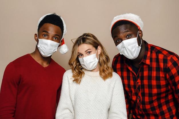 Zwei schwarze männer und eine schöne kaukasische junge frau in weihnachtsmannhüten und medizinischen masken
