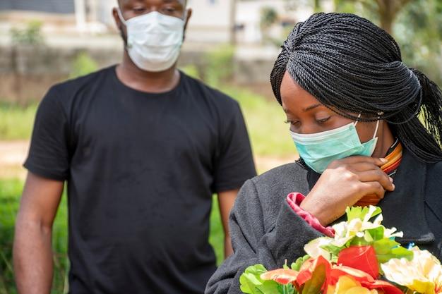 Zwei schwarze menschen, die um coronavirus trauern, gesichtsmasken tragen und sich physisch distanzieren