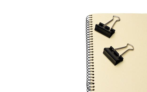Zwei schwarze metallbinder-büroklammern auf einem notizbuch mit leerraum