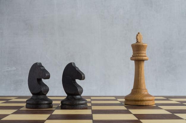 Zwei schwarze pferde greifen einen weißen könig auf dem schachbrett an