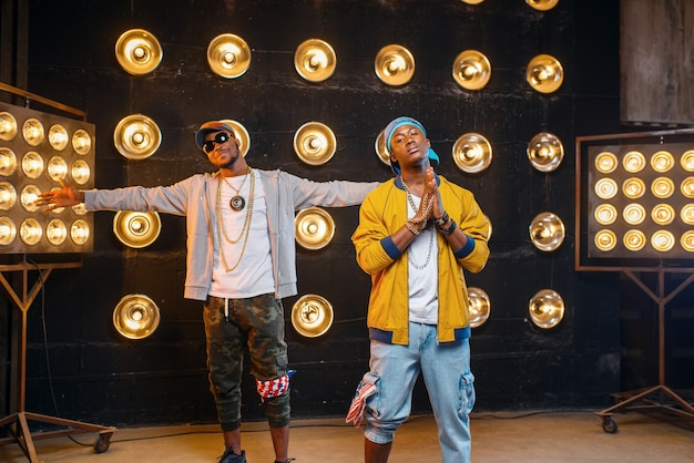 Zwei schwarze rapper in mützen, künstler posieren auf der bühne