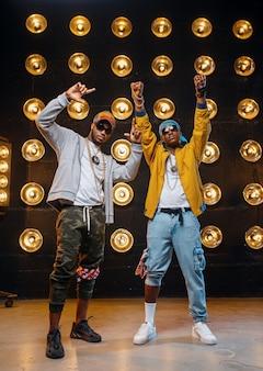 Zwei schwarze rapper in mützen, leistung auf der bühne mit scheinwerfern an der wand. rap-darsteller vor ort mit lichtern, underground-musikkonzert im urbanen stil