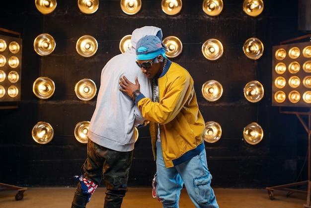 Zwei schwarze rapper in mützen umarmen sich auf der bühne, leistung im club mit scheinwerfern an der wand. rap-darsteller vor ort mit lichtern, underground-musikkonzert im urbanen stil