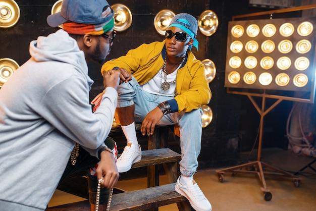 Zwei schwarze rapper mit sonnenbrille, leistung auf der bühne mit scheinwerfern