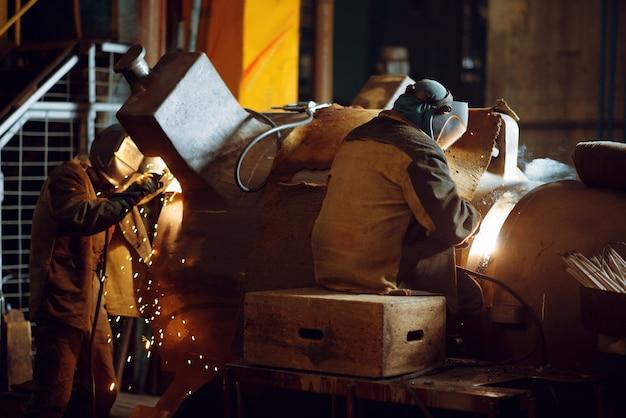 Zwei schweißer in masken arbeiten mit großen metallrohren in der fabrik, schweißfertigkeit. metallverarbeitende industrie, industrielle herstellung von stahlprodukten