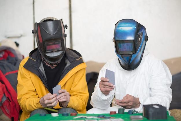 Zwei schweißer in schweißmasken spielen poker