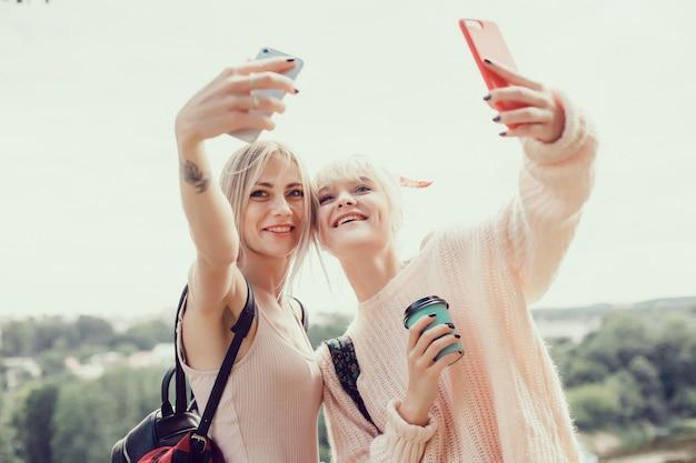 Zwei schwestern der jungen mädchen, die auf der straße aufwerfen, machen selfie