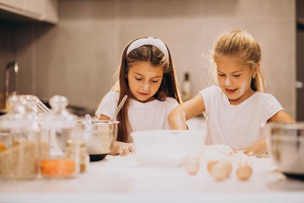 Zwei schwestern der kleinen mädchen, die an der küche kochen