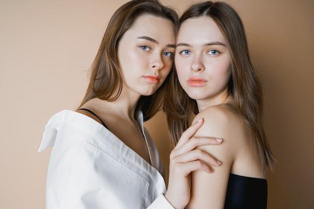 Zwei schwestern der mode modellieren die schönen nackten mädchen, die kamera betrachten