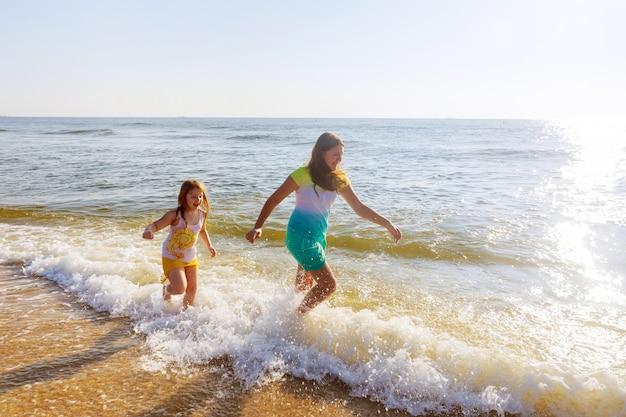 Zwei schwestern, die am strand bei sonnenuntergang spielen