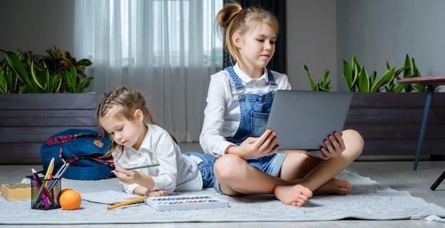 Zwei schwestern, die auf dem boden im wohnzimmer mit laptop liegen, spielen und zeichnen