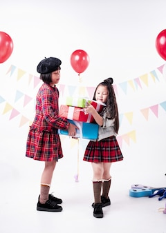 Zwei Schwestern, die Geschenkbox zusammenhalten, genießen und glückliches Gefühl, an der Partei