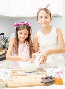 Zwei schwestern, die in einer großen weißen schüssel teig auf der küche machen