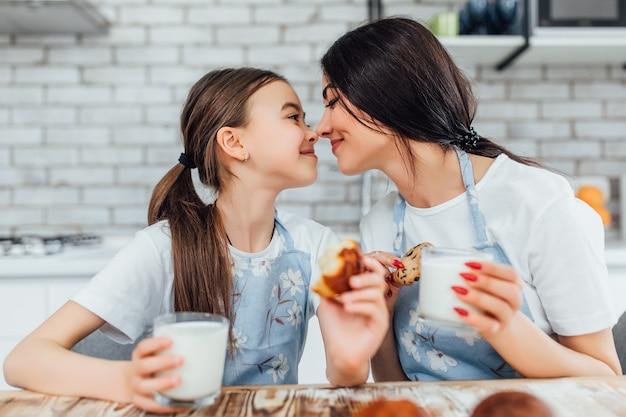 Zwei schwestern, die lächeln, während sie ihre muffins probieren und milch trinken