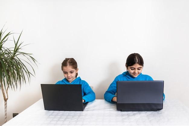 Zwei schwestern, eine blondine und eine brünette zu hause in schuluniform mit blauem sweatshirt, die zu hause mit laptop hausaufgaben lernen