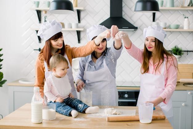 Zwei schwestern, großmutter und kleine kleine tochter, die feiertagstorte in der küche zum muttertag kochen, lässige lifestyle-fotoserie im realen innenraum