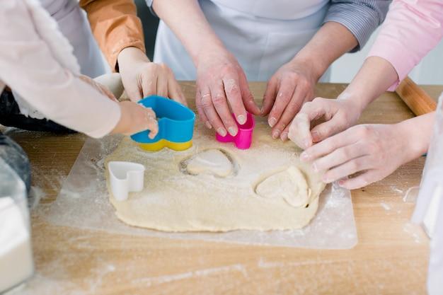 Zwei schwestern, großmutter und kleine kleine tochter kochen in der küche zum muttertag, lifestyle-fotoserie in hellem wohnraum. hände, die herzplätzchen vom teig vom muttertag schneiden