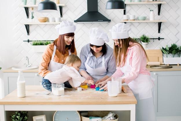 Zwei schwestern, großmutter und kleine kleine tochter kochen in der küche zum muttertag, lifestyle-fotoserie in hellem wohnraum