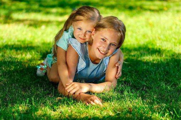 Zwei schwestern im park. der jüngere umarmt den älteren.