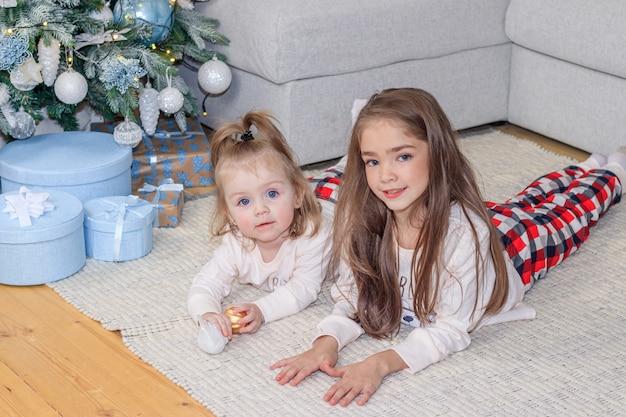 Zwei schwestern in der nähe des weihnachtsbaumes. süße kleine mädchen. wohnkomfort. weihnachtsdekoration.