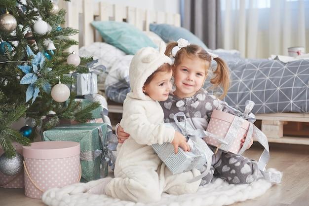 Zwei schwestern in einem weihnachten verzierten studio in den pastellfarben