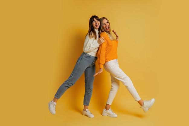 Zwei schwestern in stilvoller herbstkleidung, die sich auf gelb amüsieren. volle länge.
