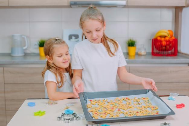 Zwei schwestern machen in der küche hausgemachte kekse.