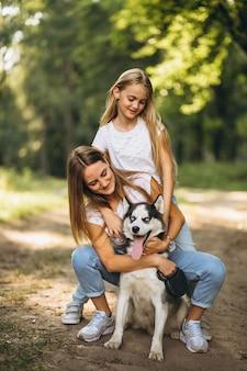Zwei schwestern mit ihrem hund im park