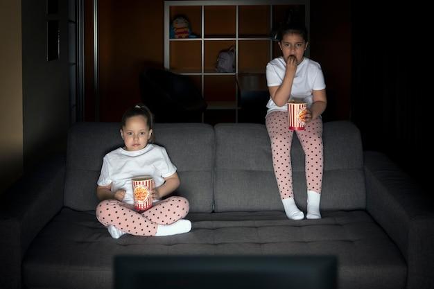 Zwei schwestern schauen sich am abend interessiert auf der couch in einem dunklen raum eine fernsehsendung im fernsehen an.