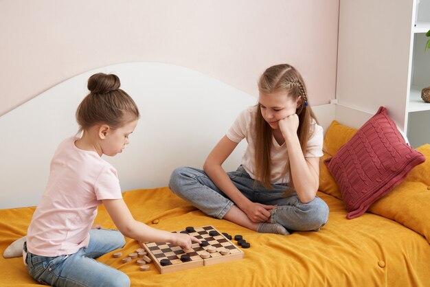 Zwei schwestern spielen dame auf einem schlechten spaß zu hause, glückliches kinderkonzept
