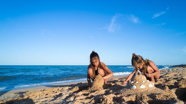 Zwei schwestern spielen mit sand an der seeküste