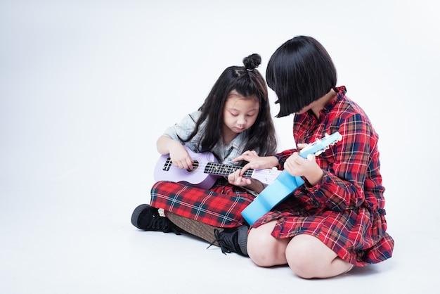 Zwei schwestern spielen zusammen ukulele, ältere schwester unterrichtet jüngere schwester