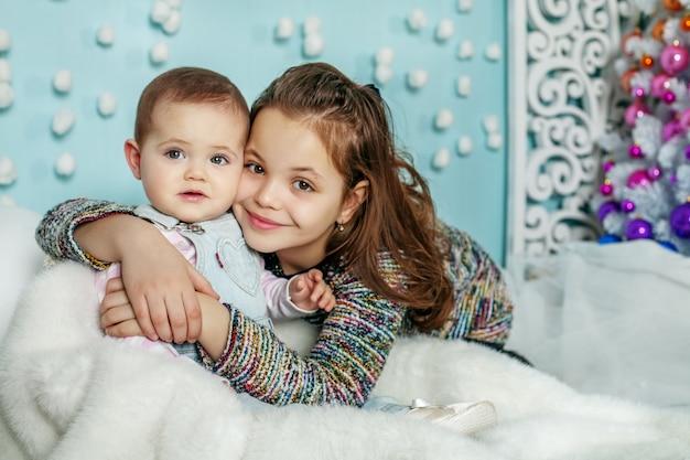 Zwei schwestern umarmen sich. kinder. das konzept der frohen weihnachten