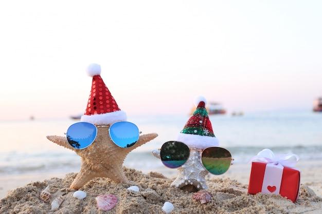 Zwei seesterne am meer strand mit sonnenbrille und nikolausmütze für frohe weihnachten und neujahr