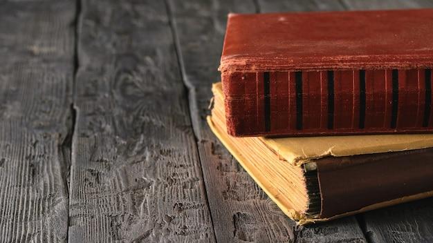 Zwei sehr alte bücher auf einem schwarzen holztisch. literatur der vergangenheit.
