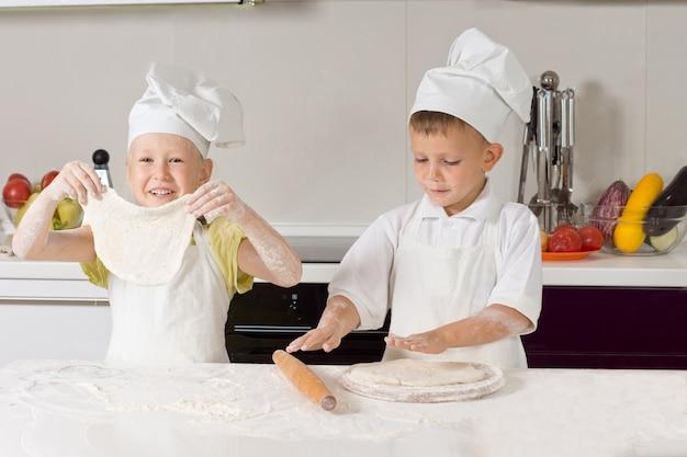Zwei sehr junge chefs, die pizzateig auf weißem holztisch platt machen.