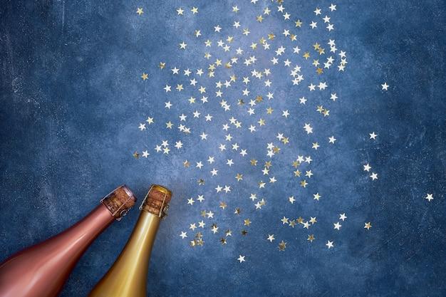Zwei sektflaschen mit goldenen konfetti auf blauem hintergrund.
