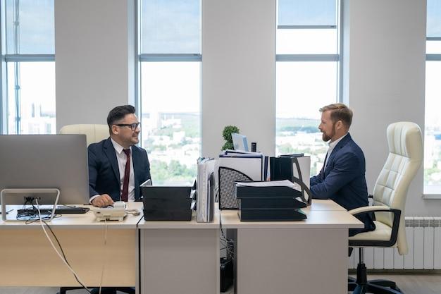 Zwei selbstbewusste geschäftsleute, die im büro arbeiten