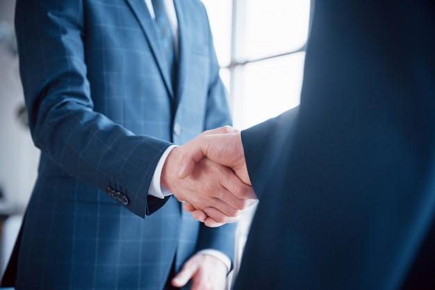 Zwei selbstbewusste geschäftsleute, die während eines treffens im büro, gruß- und partnerkonzept händeschütteln