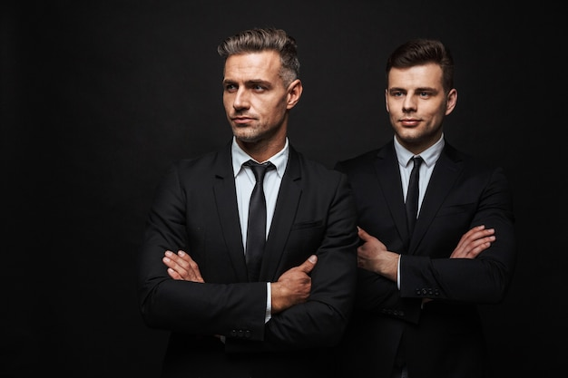 Zwei selbstbewusste, gutaussehende geschäftsleute im anzug, die isoliert über einer schwarzen wand stehen, die arme verschränkt