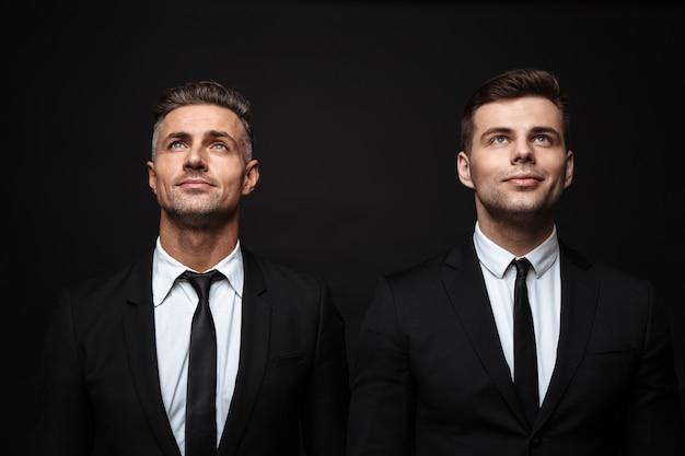 Zwei selbstbewusste, gutaussehende geschäftsleute im anzug stehen isoliert über einer schwarzen wand und schauen nach oben