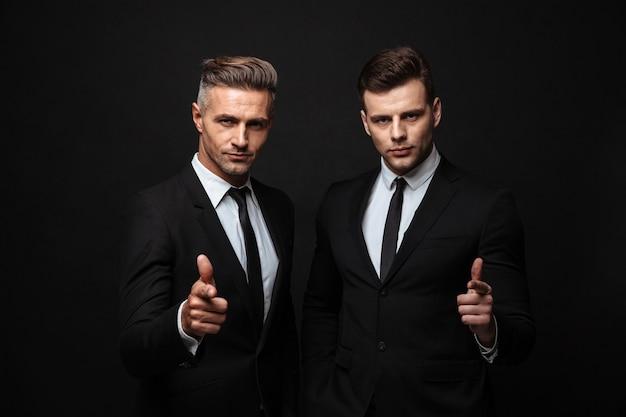 Zwei selbstbewusste, gutaussehende geschäftsleute im anzug stehen isoliert über einer schwarzen wand und zeigen auf die kamera