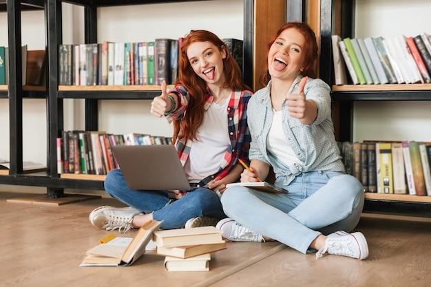 Zwei selbstbewusste teenager-mädchen, die auf einem boden am bücherregal sitzen
