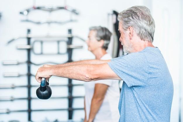 Zwei senioren arbeiten an ihrem körper, um gemeinsam im fitnessstudio mit einem gewicht gesund zu sein - ein paar reife leute, die trainieren