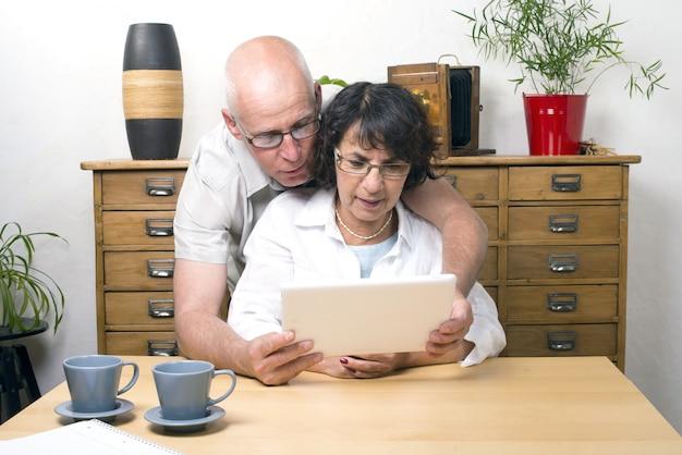 Zwei senioren spielen mit einem tablet-computer